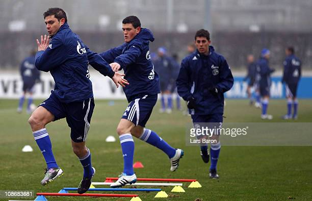 Angelos Charisteas warms up with team mates Kyriakos Papadopoulos and Danilo Avelar during a FC Schalke 04 training session at Schalke 04 training...