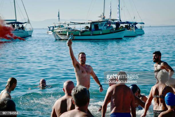 Angelos Filoxenidis holds the wooden cross after retrieving it from the sea off a beach of Athens' coastal suburb on January 6 during the annual...