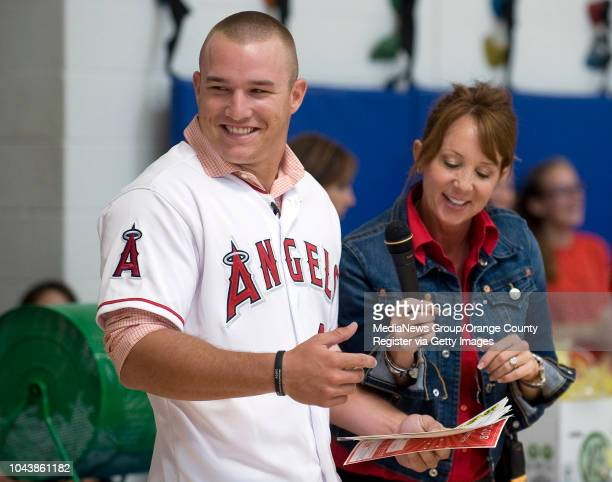 Angels outfielder Mike Trout laughs while pulling raffle numbers with Thurston Middle School principal Jenny Salberg during an assembly at the Laguna...