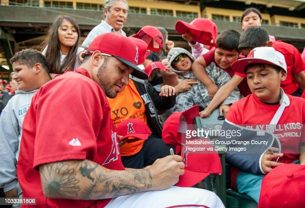 Angel's pitcher Hector Santiago left signs a cap as students attending the 6th annual Angels antigang challenge at Angel Stadium jostle for position...