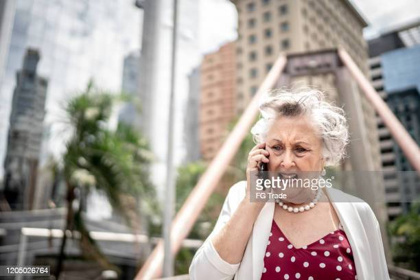anger senior businesswoman walking and talking on mobile phone in the city - complaining stock pictures, royalty-free photos & images