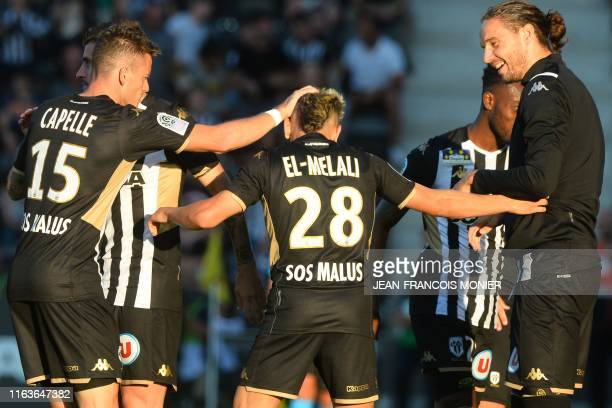 Angers' Algerian forward Farid El Melali is congratulated after scoring a goal by Angers' French midfielder Pierrick Capelle and Angers' French...