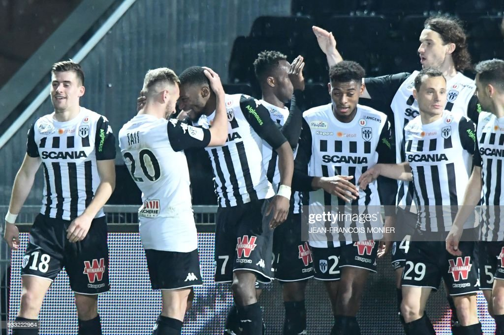 Angers' Cameroonian forward Karl Toko Ekambi (3L) is congratulated by Angers' French midfielder Flavien Tait (2L) after scoring during the French L1 Football match between Angers (SCO) and Caen (SMC), on March 17, 2018, in Raymond-Kopa Stadium, in Angers, northwestern France. PHOTO / Jean-Francois MONIER