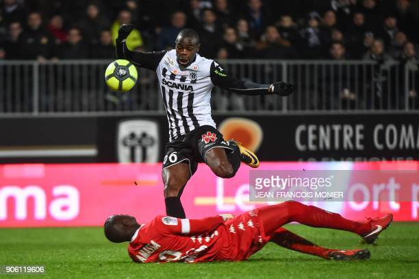 Anger's Congolese midfielder Prince Oniangue jumps over Troyes' MalianFrench goalkeeper Mamadou Samassa during the French L1 Football match between...