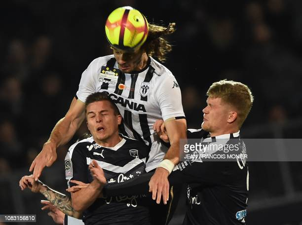 Angers' Croatian defender Mateo Pavlovic vies with Bordeaux' French forward Nicolas De Preville and Bordeaux' Danish forward Andreas Cornelius during...