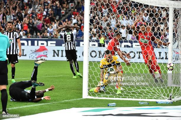 Angers' French defender Issa Cissokho falls as Angers' French goalkeeper Alexandre Letellier and Paris SaintGermain's Brazilian defender Marquinhos...