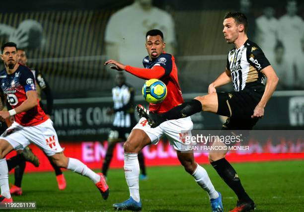 Angers' French defender Romain Thomas fights for the ball against Lille's Brazilian defender Gabriel dos Santos Magalhaes during the French L1...
