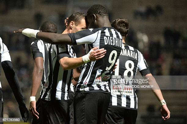 Angers' French forward Famara Diedhiou is congratulated by teammates after scoring a goal during the French L1 football match between Angers and...