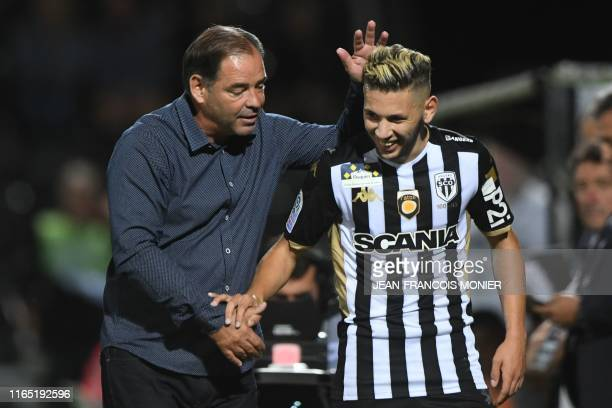 Angers' French head coach Stephane Moulin congratulates Angers' Algerian forward Farid El Melali after scoring a goal during the French L1 football...