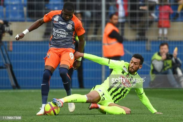 Angers' French midfielder Angelo Fulgini vies for the ball with Montpellier's Cameroonian midfielder Ambroise Oyongo during the French L1 football...