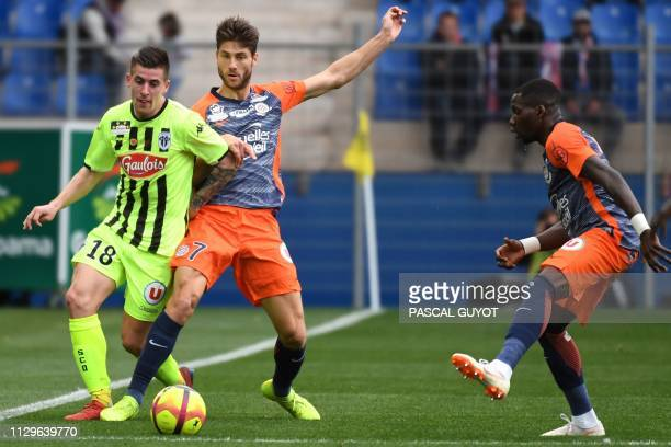Angers' French midfielder Baptiste Santamaria vies for the ball with Montpellier's French midfielder Paul Lasne and Montpellier's Cameroonian...
