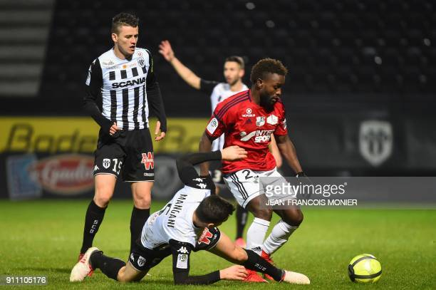 Angers' French midfielder Thomas Mangani tackles Amiens' Colombian forward Stiven Mendoza as Angers' French midfielder Pierrick Capelle looks on...