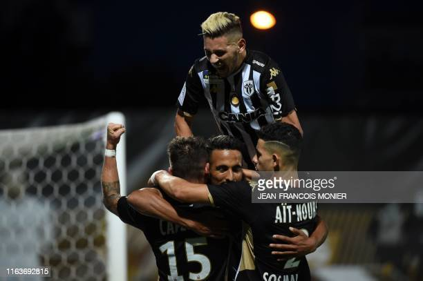 Angers' Moroccan' forward Rachid Alioui is congratulated by Angers' French midfielder Pierrick Capelle and Angers' Algerian forward Farid El Melali...