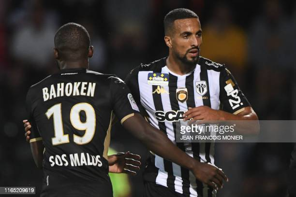 Angers' Moroccan forward Rachid Alioui leaves the field and walks next to Angers' French Cameroonian forward Stephane Bahoken during the French L1...