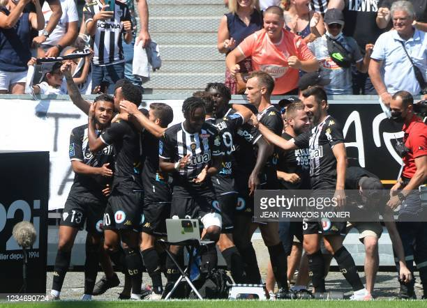 Angers' Moroccan midfielder Sofiane Boufal is congratulated by his teammates after he scored a goal during the French L1 football match between...