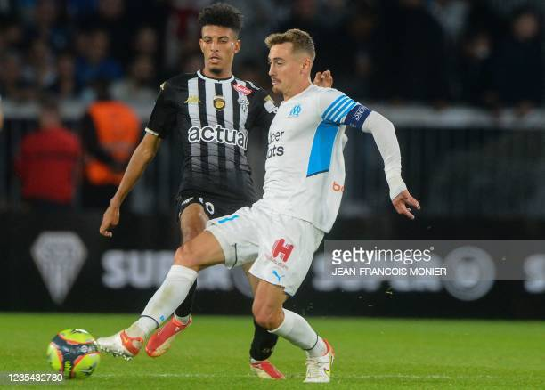 Angers' Morrocan midfielder Azz-eddine Ounahi fights for the ball with Marseille's French defender Valentin Rongier during the French L1 football...