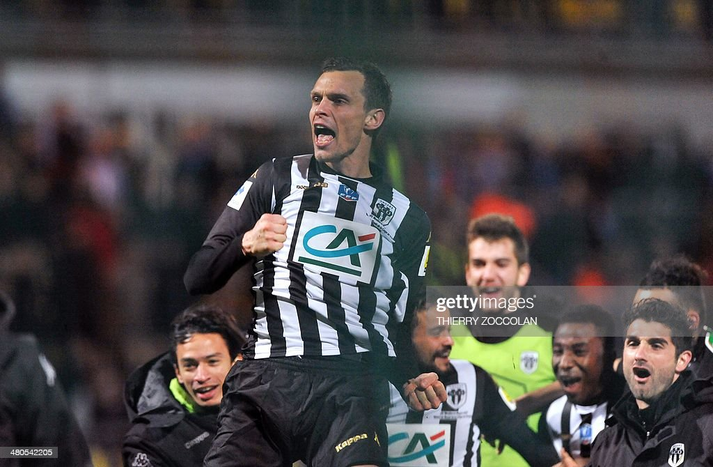 Angers' Romain Thomas and team mates celebrate after winning their French Cup quarter final football match between Moulins and Angers on March 25, 2014 at the Jean Laville stadium in Gueugnon.