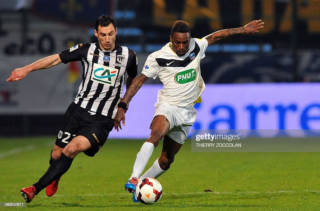 Angers' Yohan Eudeline (L) vies with Moulins' Pedro Kamata (R) during the French Cup quarter final football match between Moulins and Angers on March 25, 2014 at the Jean Laville stadium in Gueugnon.