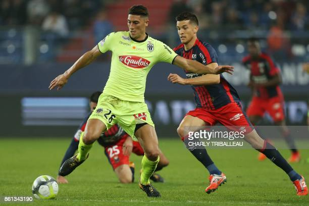 Angers's Algerian defender Mehdi Tahrat vies for the ball with Caen's Belgian midfielder Stef Peeters during the French L1 football match between...