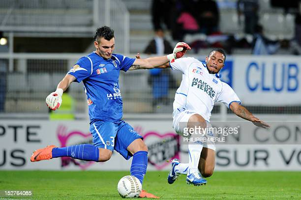 Angers's French goalkeeper Alexander Letellier vies with Auxerre's French defender Vincent Acapandie during the French League Cup football match...