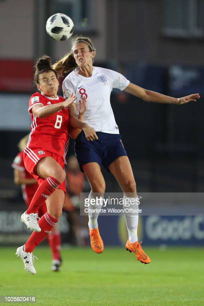Angharad James of Wales and Jill Scott of England go up for a header during the FIFA Women's World Cup Qualifier at Rodney Parade Stadium on August...