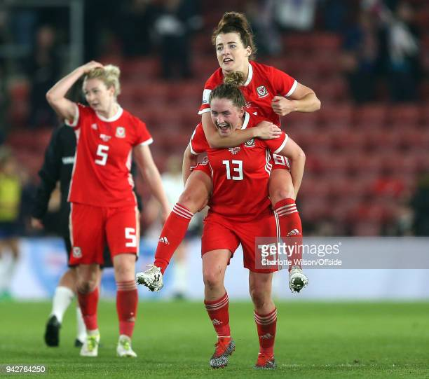 Angharad James of Wales jumps on the back of Rachel Rowe of Wales as they celebrate their 0-0 draw during the Womens World Cup Qualifier between...