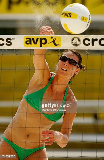 Angie Akers spikes the ball against Heather Lowe and Ashley Ivy while playing with Brooke Hanson during the AVP Louisville Open May 26, 2007 at...