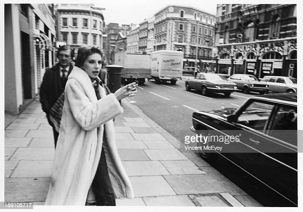 Angie Bowie leaves St Martins Lane Theatre Cabaret holding a glass of wine London 1977