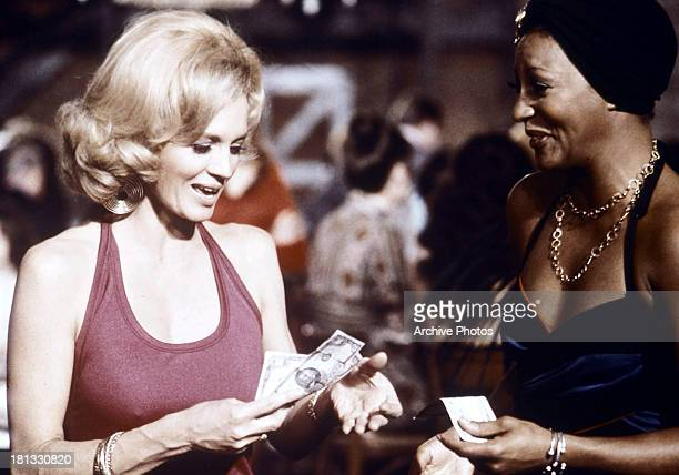 Angie Dickinson holds money in a scene from the TV series 'Police Woman' circa 1975