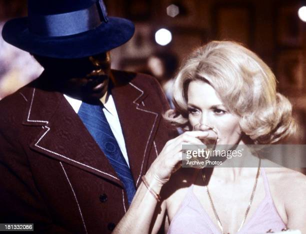 Angie Dickinson sips a drink next to a man in a scene from the TV series 'Police Woman' circa 1975