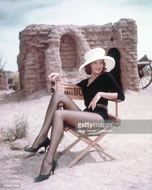 Angie Dickinson US actress wearing a black longsleeved leotard and a white wide brimmed hat relaxing in a director's chair on the set of 'Rio Bravo'...