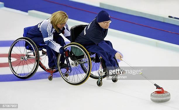 Angie Malone of Great Britain steadies team mate Michael McCreadie as he releases the stone during the Wheelchair Curling match between Great Britain...