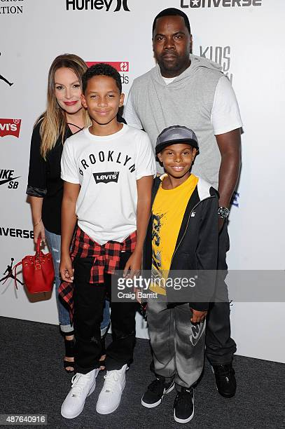 Angie Martinez and her son Nico pose with Oronde Garrett and his son Christan backstage at the Nike/Levi's Kids Rock fashion show during Spring 2016...