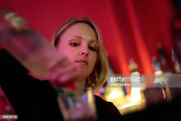 Angie Seigley pours a drink as she takes her New York Bartending School final exam December 5 2008 in New York City Seigley formerly worked at Morgan...