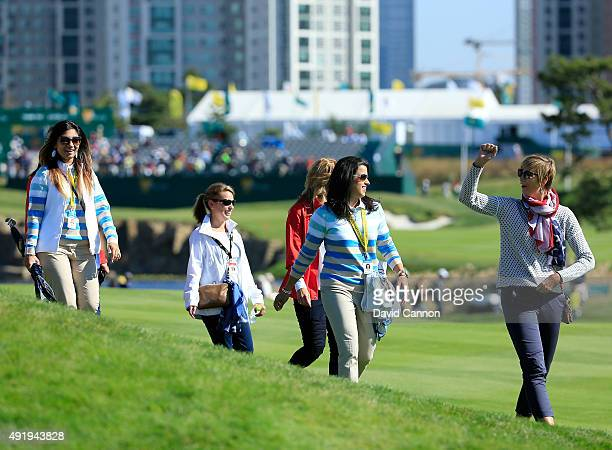 Angie Watson of the United States leads a group of team wives on the first hole during the Friday fourball matches at The Presidents Cup at Jack...
