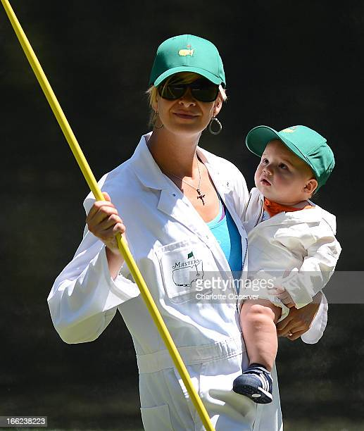 Angie Watson pulls the pin for her husband Bubba Watson as their son Caleb looks on during the Par 3 Contest at the Masters at Augusta National Golf...