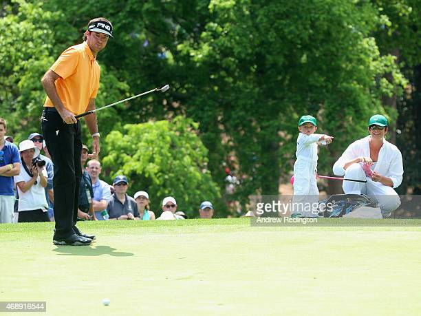 Angie Watson waits with her son Caleb as Bubba Watson watches a putt during the Par 3 Contest prior to the start of the 2015 Masters Tournament at...