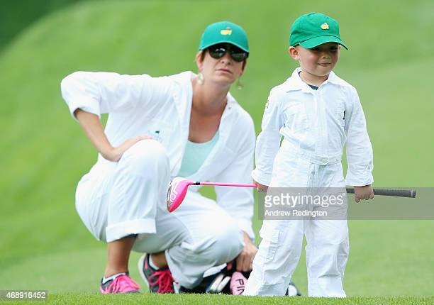 Angie Watson waits with her son Caleb during the Par 3 Contest prior to the start of the 2015 Masters Tournament at Augusta National Golf Club on...