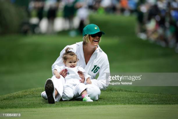 Angie Watson, wife of Masters Champion Bubba Watson, and his daughter Dakota laugh during the Par 3 Contest at Augusta National Golf Club on...