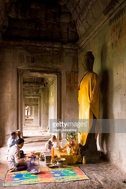 Angkor, Cambodia, August 8; 2007. -- A family is praying in Angkor Wat temple. Angkor Wat is the largest Hindu temple complex in the world. The...