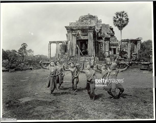 Angkor, Cambodia: Portrait of temple dancers at Angkor. They are shown posing in costume outside the temple ruins. Undated photograph.