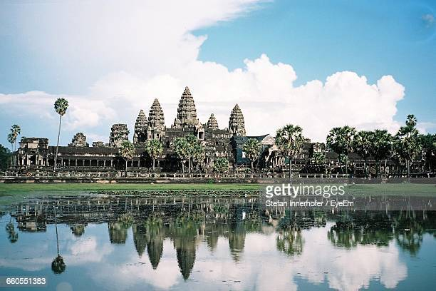 Angkor Wat Temple By Lake Against Cloudy Sky