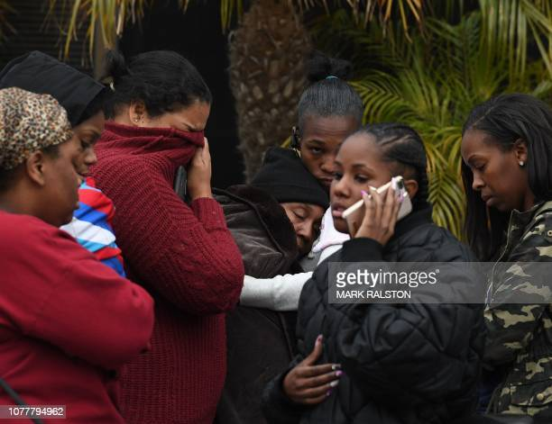 Anglean Hubbarb grieves outside the Gable House Bowl center after 3 men were killed and 4 injured in a shooting at the bowling alley in Torrance...