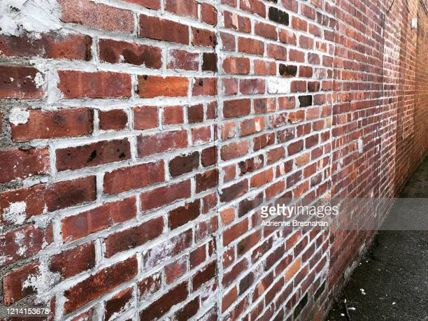 angled view looking down a brick alleyway - brick wall stock pictures, royalty-free photos & images