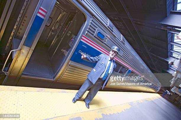Angled view of conductor at Amtrak train platform announces All Aboard at East Coast train station on the way to New York City New York Manhattan New...