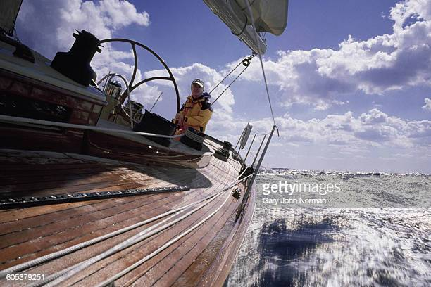Angled view of mature man sailing yacht on choppy water