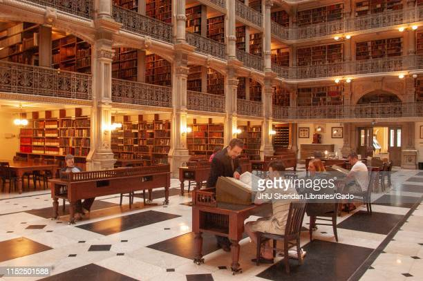 Angled view of patrons looking at books on the ground floor of the George Peabody Library at the Johns Hopkins University, Baltimore, Maryland, June...