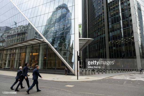 Angled view of the cityscape and skyline reflections looking towards 1 St Mary Axe aka the Gherkin as city wokers in small numbers interact in the...