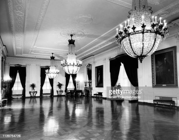 Angled view of the East Room of the White House with crystal chandeliers and portraits of George and Martha Washington on the walls Washington...