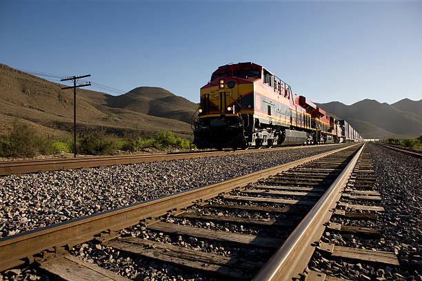 angled view of train tracks with oncoming freight train - cargo train stock pictures, royalty-free photos & images